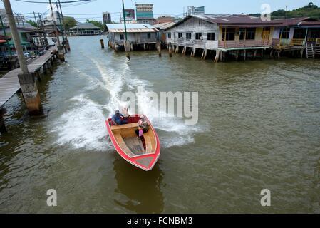 Speedboat water taxi passing walkway and shacks on stilts in Brunei River, Water Village (Kampong Ayer), Bandar - Stock Photo