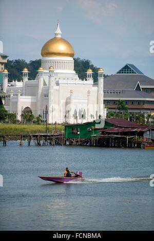 Speedboat on river with opulent Sultan Omar Ali Saifuddien Mosque next to shacks in background from Edinburgh Bridge, - Stock Photo