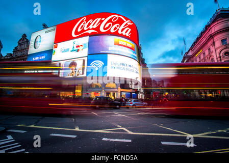 Buses and Taxis whizz past The world famous Advertising boards in Piccadilly Circus in London. - Stock Photo