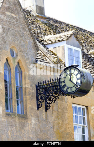 victorian aged double sided hanging wall clock with roman numerals on a side of old golden
