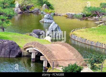 Garden path over rustic bridge in lake park with big granite rocks and green pine trees, autumn Japanese landscape - Stock Photo