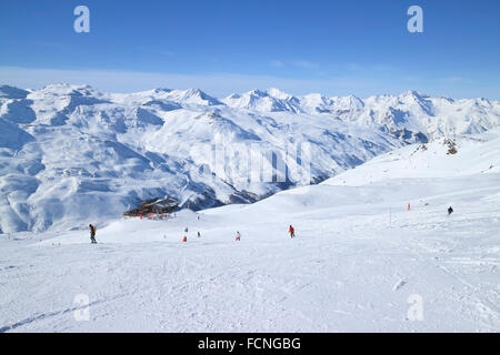 Skiers on ski slopes in high Alps resort of Three Valleys France, apres ski chalet, with snowy mountain peaks against - Stock Photo
