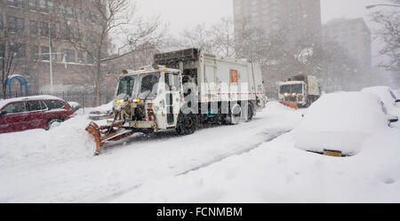 New York, USA. 23rd Jan, 2016. Dept. of Sanitation trucks plow West 26th Street, a secondary roadway, in Chelsea - Stock Photo