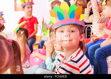 Boy in Indian headwear with group of kids - Stock Photo