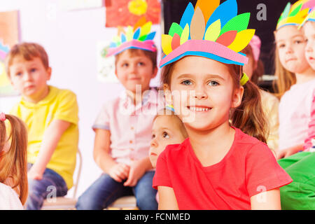 Happy little girl with handmade headwear in class - Stock Photo
