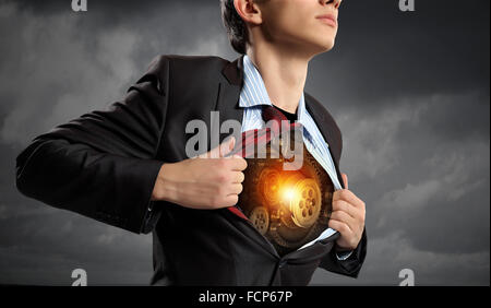 Businessman opening his shirt on chest acting like super hero - Stock Photo
