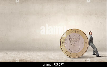 Young businessman rolling huge five euro coin - Stock Photo