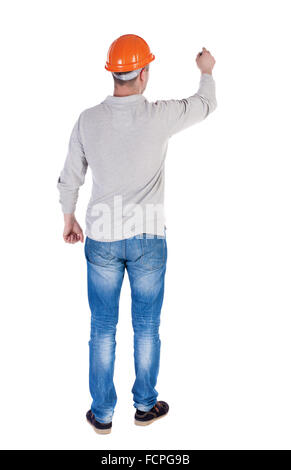 back view of writing engineer in construction helmet. Young gay in jeans draws. Rear view people collection. backside - Stock Photo