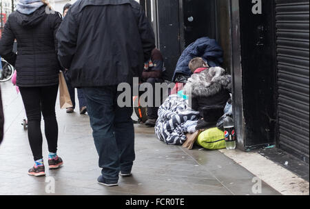 Brighton UK 24th January 2016 - Shoppers walk past some rough sleepers on the streets of Brighton today . A shrine - Stock Photo