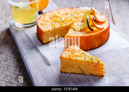 Home made whole testy orange cake on a wooden surface - Stock Photo