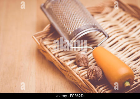 metal nutmeg hand grater and nutmegs on a wood background - Stock Photo