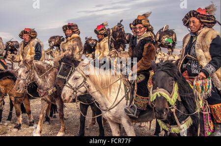 Kazakh Burkitshi hunters pose on horseback during the Mongolian Golden Eagle Festival in Olgii, Mongolia. - Stock Photo