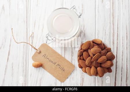 almond milk organic healthy nut vegan vegetarian drink white background wood teak rustic still life label - Stock Photo