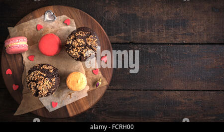 Served chocolate maffins and colorful macaroons cookies on wooden background with blank space - Stock Photo
