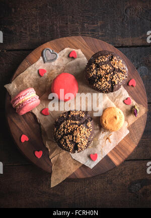 Served chocolate maffins and colorful macaroons cookies on wooden background - Stock Photo