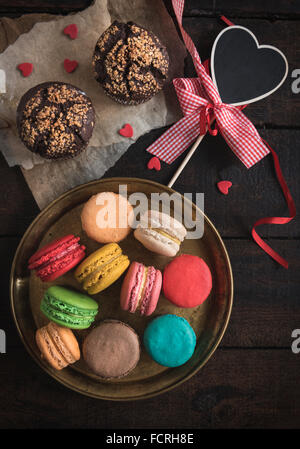 Served chocolate maffins and colorful macaroons cookies on wooden background,valentine day concept - Stock Photo