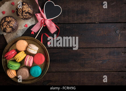 Served chocolate maffins and colorful macaroons cookies on wooden background,valentine day concept and blank space - Stock Photo