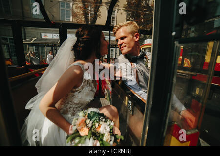 Bride and groom posing in a tour car - Stock Photo