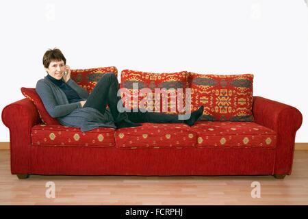 Older woman gossiping on phone, on sofa. - Stock Photo