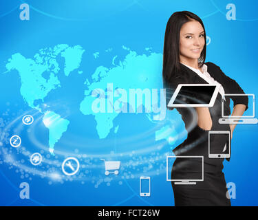 Business woman standing with tablet in hand on world map background - Stock Photo