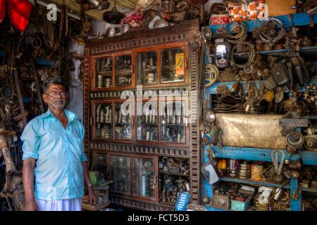 Shopkeeper Selling Various Recycled Scooter and Motorbike Parts Posing with Display Cabinet, Kerala, South India. - Stock Photo