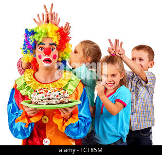 Clown holding cake on birthday with group children. - Stock Photo