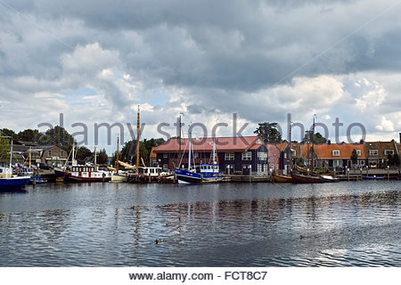 Classic wooden boats and other watercraft are moored in the harbor of the small city of Elburg, in the Netherlands. - Stock Photo