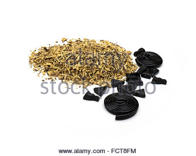 Liquorice (licorice), Glycyrrhiza glabra, with candy made from it. - Stock Photo