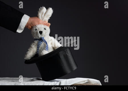 Man in suit pulling a rabbit out of the topper hat - Stock Photo