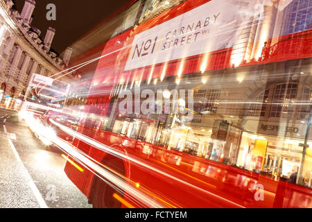 Red bus on the Regent Street in London. Blurry lights from long shutter. - Stock Photo