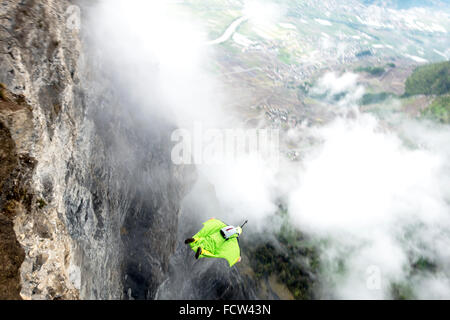 This wingsuit BASE jumper just exited from a cliff down into the valley. He'll open his parachute just before hit - Stock Photo