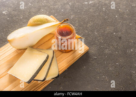 A composition of italian cheese pecorino slices with jam and pears on a wooden chopping board - Stock Photo