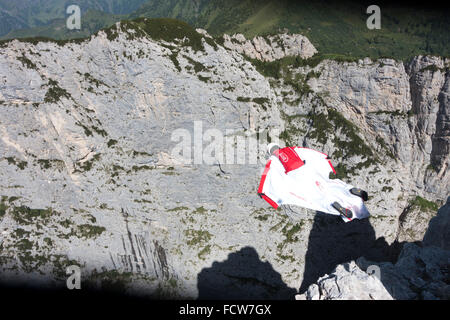 Crazy BASE jumper is flying within his wingsuit along a cliff. Thereby he's soaring with 100mph forward and has - Stock Photo