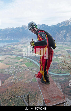 Freaky BASE jumper is ready to jump from a diving board. He checked his equipment already, to make sure the parachute - Stock Photo