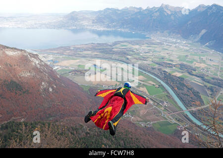 This wingsuit BASE jumper just exited from a cliff downwards. He'll open his parachute in a few seconds and hopes - Stock Photo