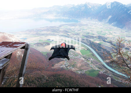 This wingsuit BASE jumper just exited from a diving board down into the valley. He'll open his parachute just before - Stock Photo