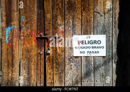 Fighting bulls danger sign on old wooden door. - Stock Photo