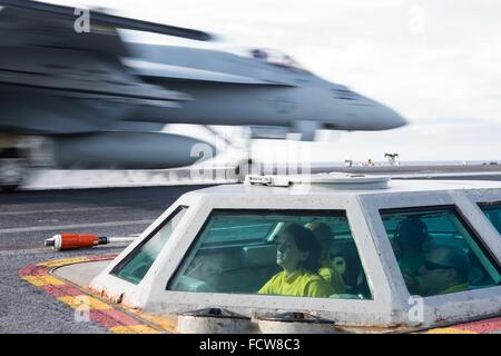 A US Navy air traffic controller launches pilot a F/A-18C Horne fighter aircraft from the bubble on the flight deck - Stock Photo
