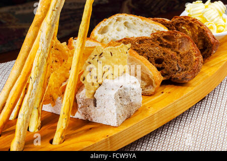 Various kinds of fresh baked bread loaves in wooden tray - Stock Photo