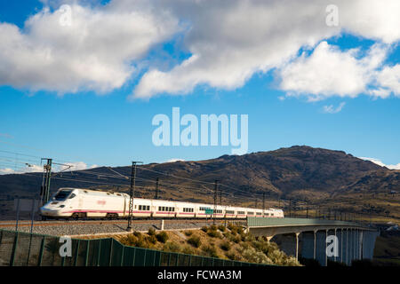 Madrid-Valladolid AVE high-speed train traveling along Arroyo del valle viaduct. Soto del Real, Madrid province, - Stock Photo