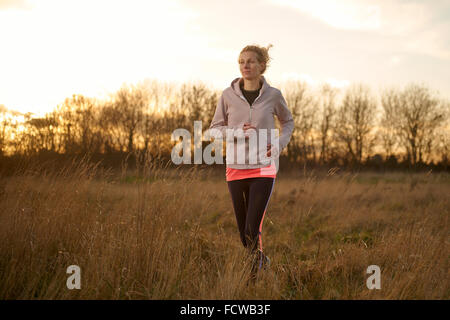A woman jogging through a field - Stock Photo