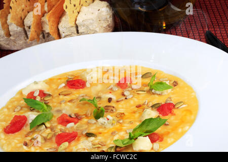 Rice soup with pumpkin seeds, cereals and tomatoes in a white bowl. - Stock Photo