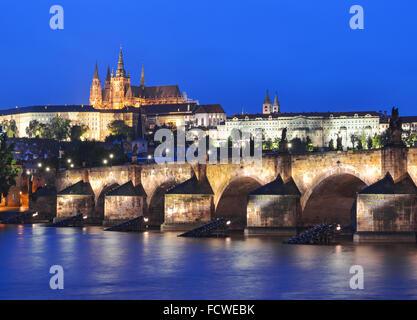 Vltava river, Charles Bridge and Prague Castle at night against a dark blue sky. Karluv Most, Prazsky hrad. Prague. - Stock Photo