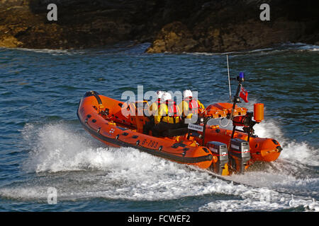 Looe RNLI's Atlantic 75 inshore lifeboat in Looe river heading out into Looe bay with a crew of three - Stock Photo