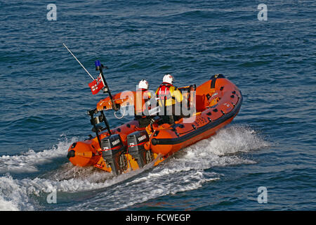 Looe RNLI's Atlantic 75 inshore lifeboat heading out into Looe bay with a crew of two. - Stock Photo
