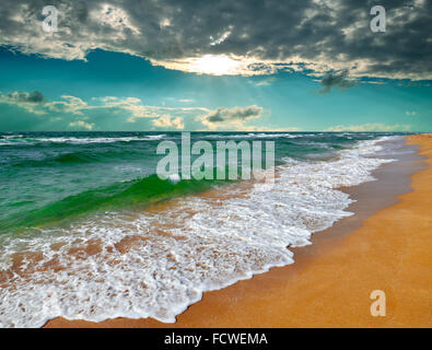 Tropical sunrise over the turquoise sea during a storm - Stock Photo