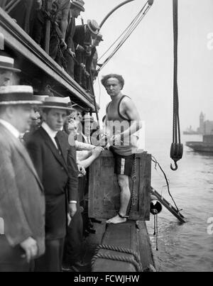 Harry Houdini stepping into a crate that will be lowered into New York Harbor as part of an escape stunt, 7th July - Stock Photo