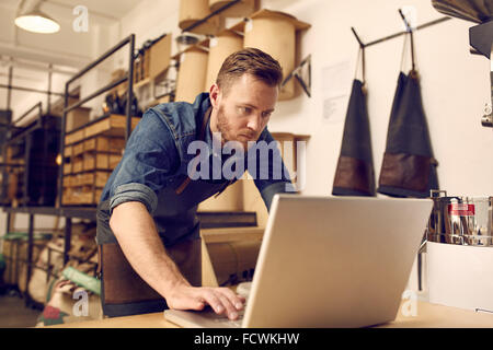 Serious young business owner using laptop in his workshop - Stock Photo