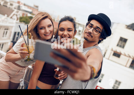 Multiracial people enjoying in party with drinks and taking a self portrait. Three young friends taking selfie with smart phone