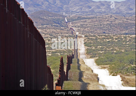 US border fence in Santa Cruz stretching into the distance leading to Nogales Sonora, Mexico and Santa Cruz County - Stock Photo